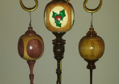 3 ornaments one with an inlay of a holly leaf